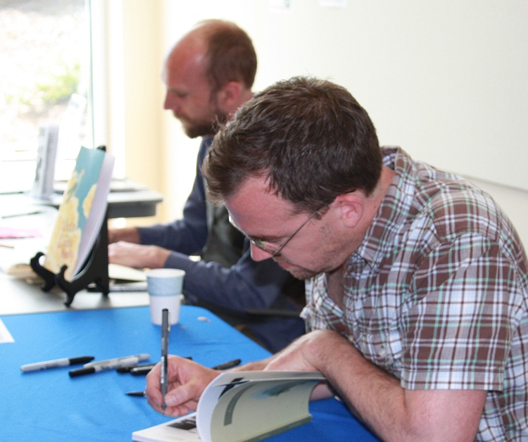 Jan Burger (left) and Jason Lutes sign books for Comics Fest attendees, 2011.